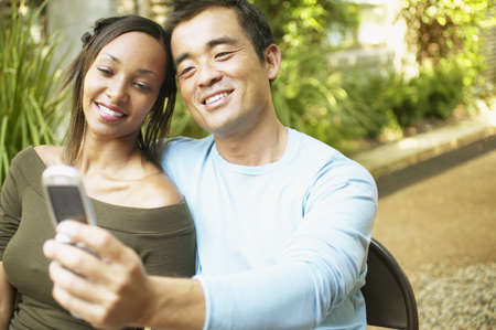 Couple sitting together looking at a mobile phone Stock Photo - 16044881