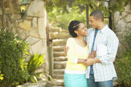 joyousness: Young couple standing together holding each other