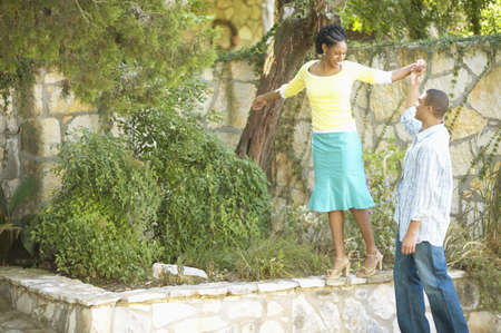 joyousness: Young woman walking on a wall holding a young mans hand