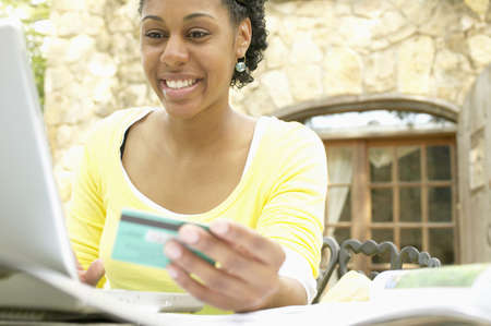 color images: Young woman sitting at a table in front of a laptop holding a credit card smiling