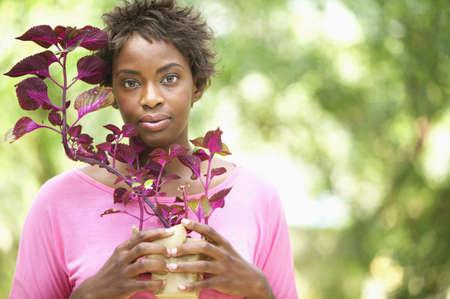 color images: Portrait of a young woman holding a plant
