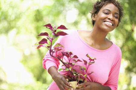 color images: Young woman holding a plant smiling