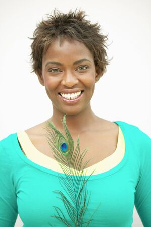 Portrait of a young woman standing holding a peacock feather smiling Stock Photo