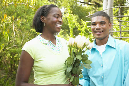 Young couple standing together holding a bunch of flowers Stock Photo - 16044927
