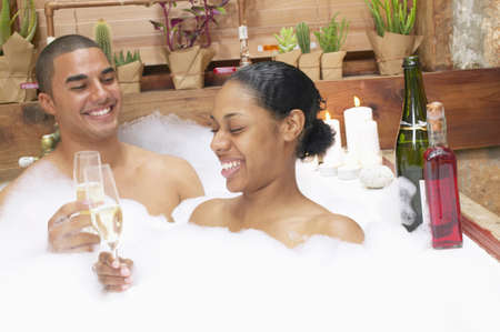 race relations: Young couple together in a bubble bath toasting with champagne