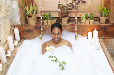 Portrait of young woman in a bubble bath smiling