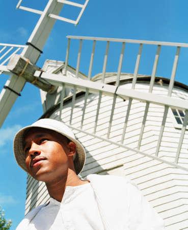 young man standing: Basso angolo di vista di un giovane uomo in piedi vicino a un mulino a vento