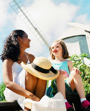 Young woman and a young girl sitting together on a step talking Stock Photo - 16044954