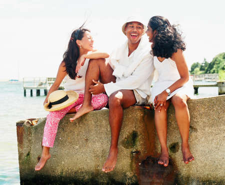 Young man and two young women sitting on a wall talking Stock Photo - 16044956