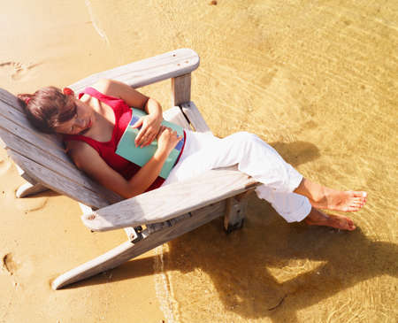 restfulness: High angle view of a young woman sitting on a beach chair