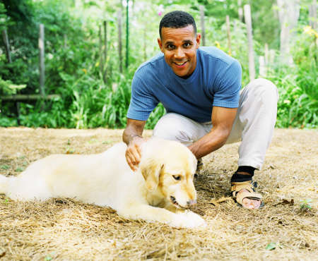 mid adult man: Retrato de un hombre de mediana edad que acaricia un perro de mascota
