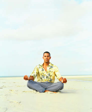 chinos: Young man sitting on sand meditating