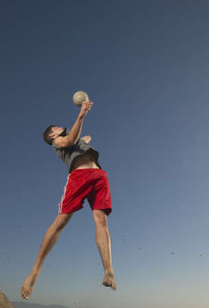 Low angle view of a young man jumping up in the air playing volleyball Stock Photo