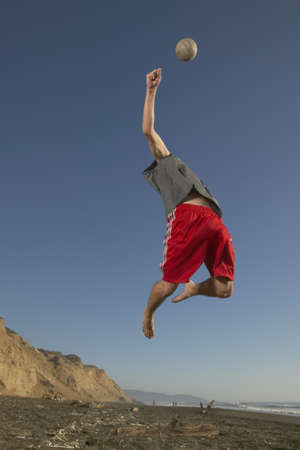 Low angle view of a young man jumping up in the air reaching for a volleyball