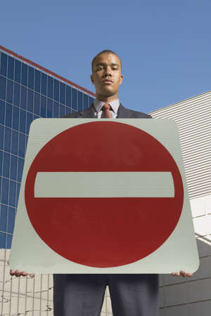 powerfully: Portrait of a young man holding a no entry signboard