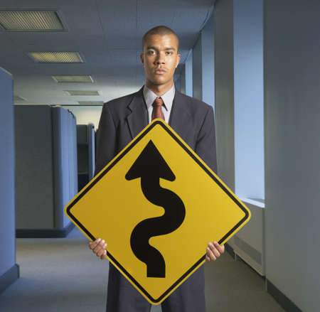Portrait of young man holding a curved road ahead signboard