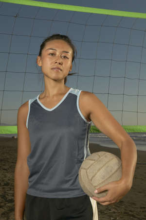 effrontery: Portrait of a young woman holding a volley in front of a net