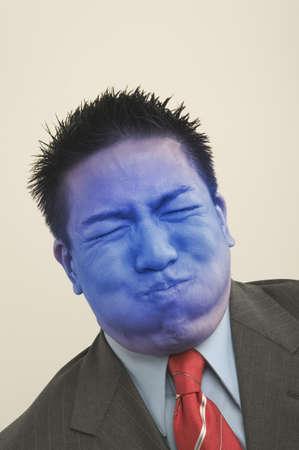 indelible: Close-up of a businessman turning blue LANG_EVOIMAGES