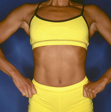 effrontery: Close-up of a the torso of a muscular young woman LANG_EVOIMAGES