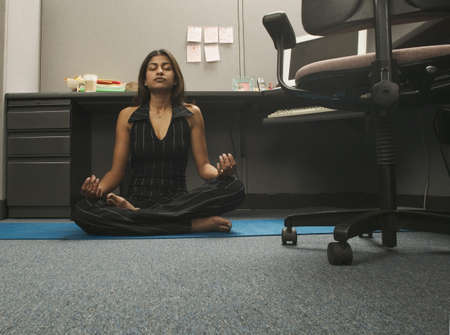 Portrait of a young woman meditating on the floor of an office LANG_EVOIMAGES
