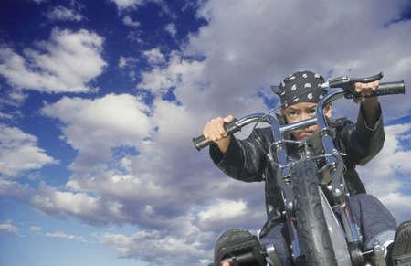 determines: Basso angolo di vista di un giovane ragazzo in sella a una motocicletta giocattolo