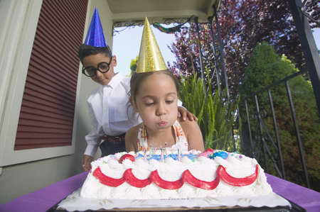 formalize: Low angle view of a young girl blowing out birthday candles with a young boy standing behind her