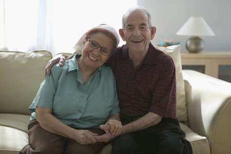 ebullient: Portrait of a senior couple sitting on a couch together