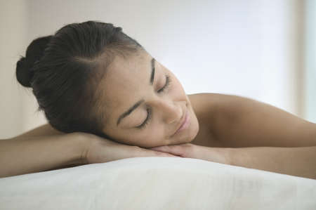 Young woman lying on a bed Stock Photo - 16045010