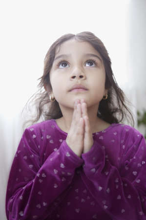 religious clothing: Young girl praying with her hands together