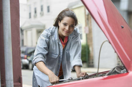 chirpy: Portrait of a mid adult woman leaning over a cars engine bay,