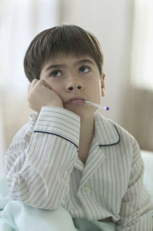 ennui: A boy sitting with a thermometer in his mouth