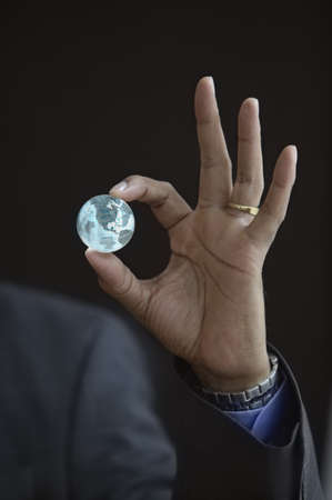 holding close: Close-up of a persons hand holding a glass globe