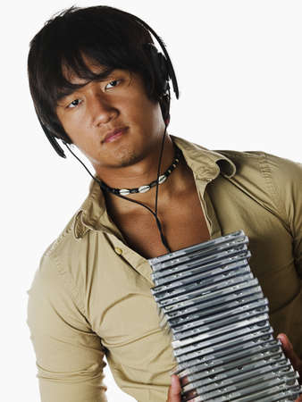 Portrait of a young man wearing headphone holding a stack of compact discs Stock Photo - 16045054