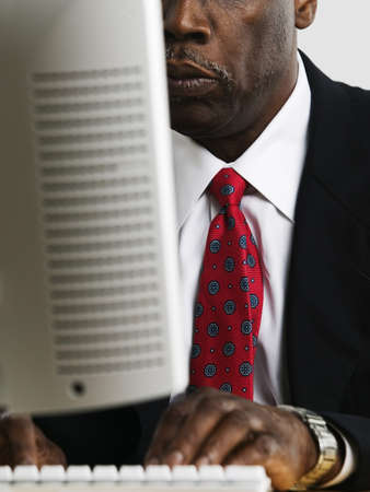 Elderly businessman operating a computer