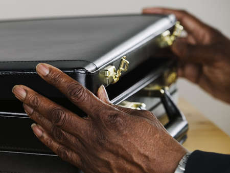 Businessmans hands opening a briefcase LANG_EVOIMAGES