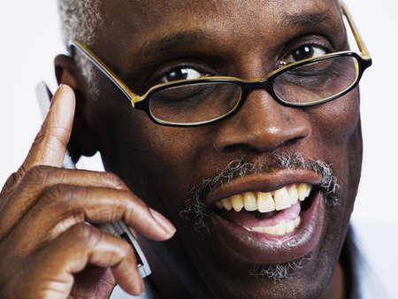 expressional: Portrait of an elderly man talking on a mobile phone smiling LANG_EVOIMAGES
