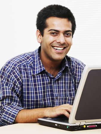 Portrait of a young man sitting in front of a laptop looking at camera smiling Stock Photo - 16045077