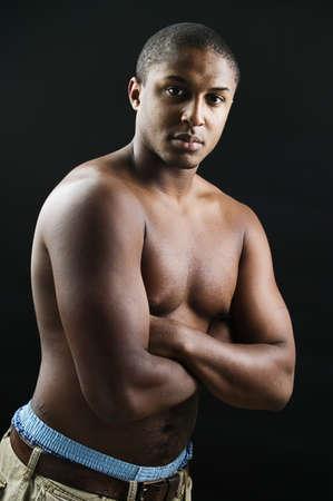 determines: Ritratto di un ragazzo adolescente in piedi petto nudo con le braccia conserte LANG_EVOIMAGES