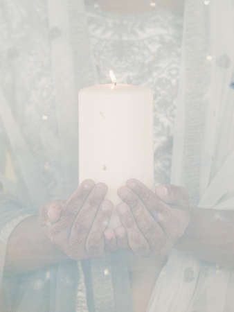 Young woman holding a lit candle Stock Photo - 16045096