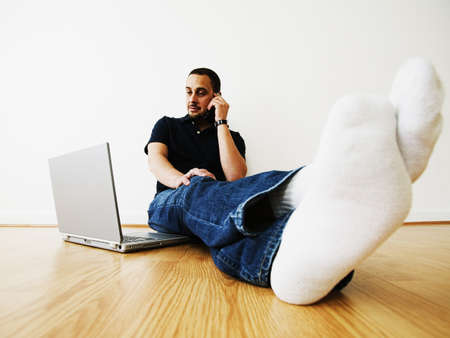 Man sitting on the floor talking on a mobile phone with a laptop in front Stock Photo - 16045097