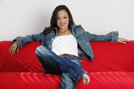 teenaged: Portrait of a teenage girl sitting on a couch