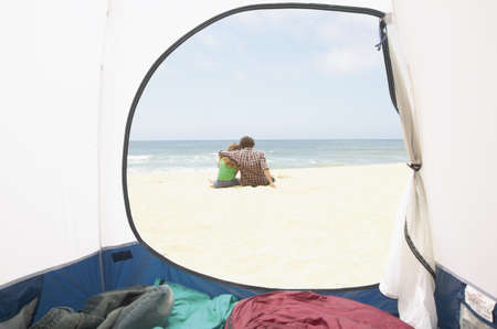 anecdote: Rear view of a teenage couple sitting on beach LANG_EVOIMAGES