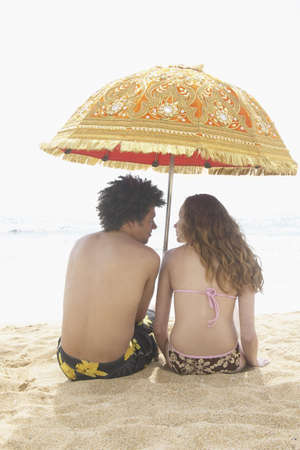 anecdote: Rear view of a teenage couple sitting on the beach LANG_EVOIMAGES