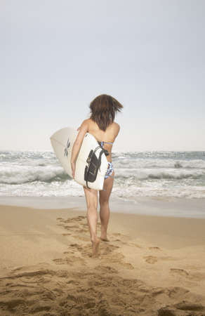 Rear view of a young woman carrying a surfboard walking on the beach Stock Photo - 16045141