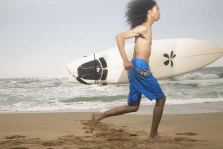 effrontery: Side profile of a teenage boy running holding a surfboard