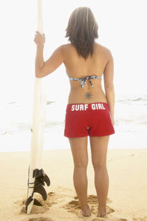 aplomb: Rear view of a teenage girl standing on the beach holding a surfboard LANG_EVOIMAGES
