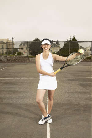 credence: Portrait of a young woman holding a tennis racket LANG_EVOIMAGES