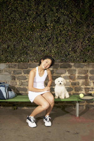 afflict: Young woman sitting on a bench with a pet dog LANG_EVOIMAGES