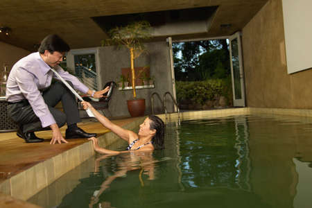 horseplay: Mid adult women in a swimming pool puling a mans by his tie