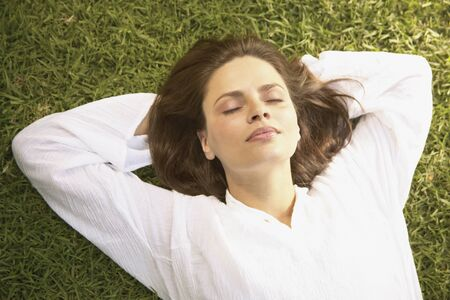 Young woman lying on a lawn 스톡 콘텐츠